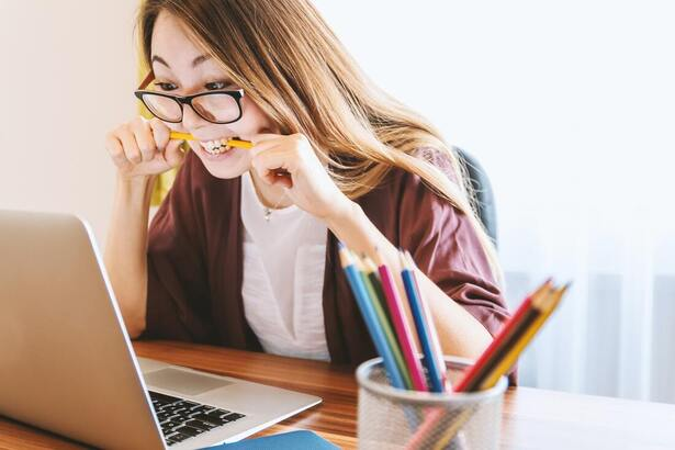 Lady with glasses sat behind a laptop chewing on a pencil in a stressful manner