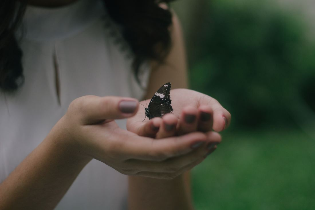 Photo of young woman holding a butterlfy in her hands. Photo by John Reign Abarintos.